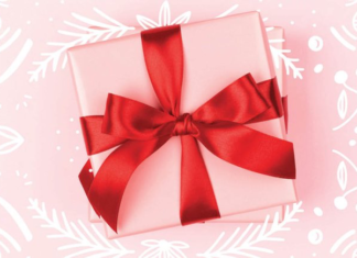 Pink gift with a red bow on a pink background
