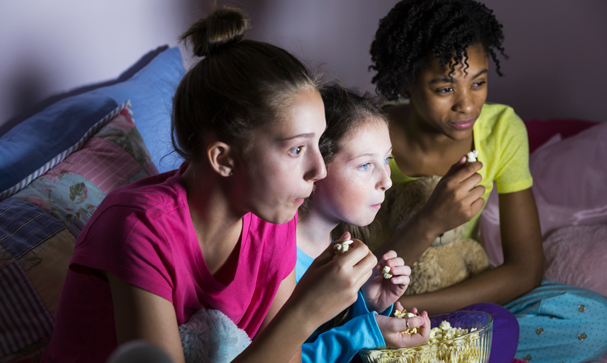 Three girls eating popcorn