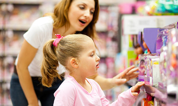 Little girl looking at toys with woman in the background