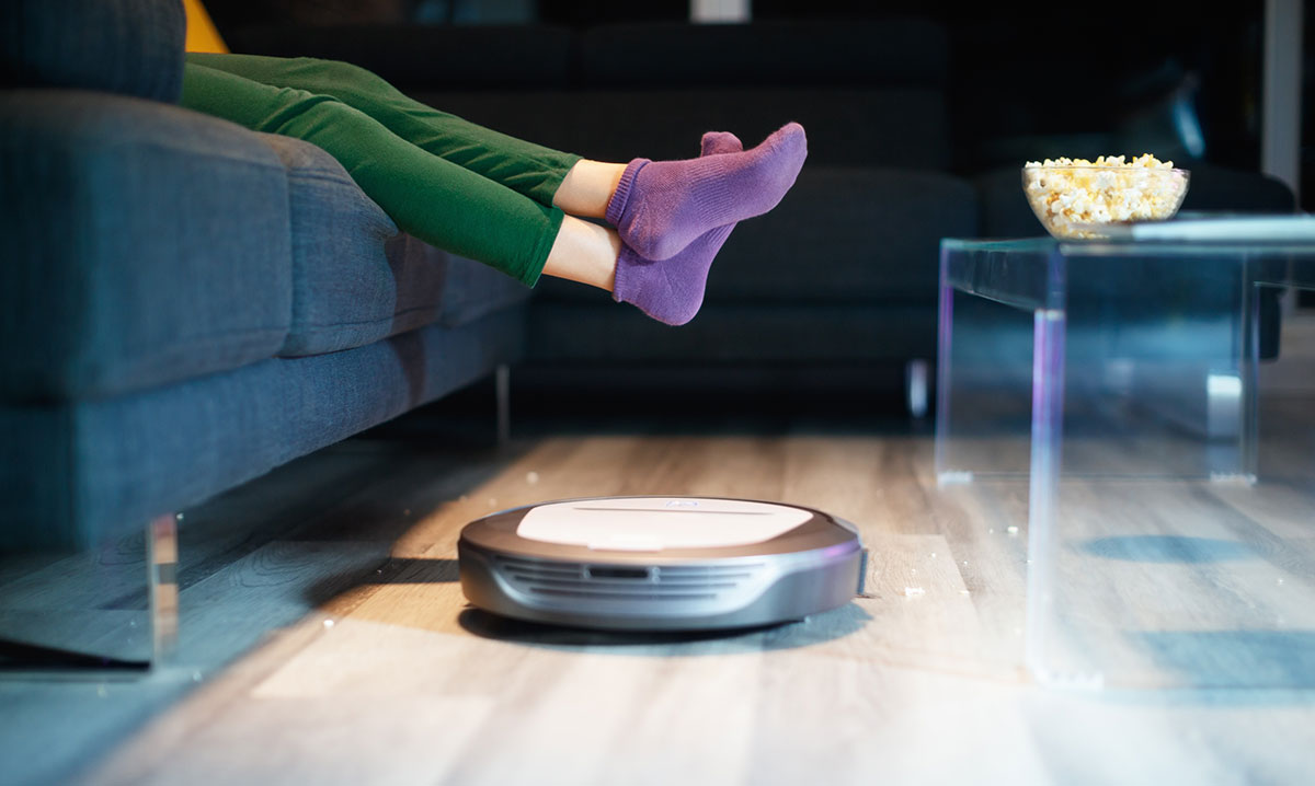 A robot vacuum cleaners rolling under a person's feet in purple socks