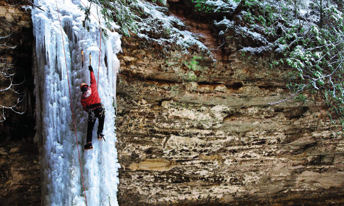 A person climbing a frozen waterfall in michigan