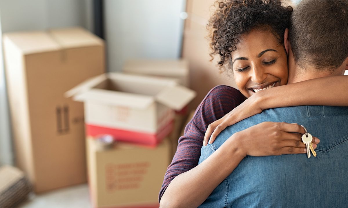 Woman hugging man in front of card boxes while holding keys