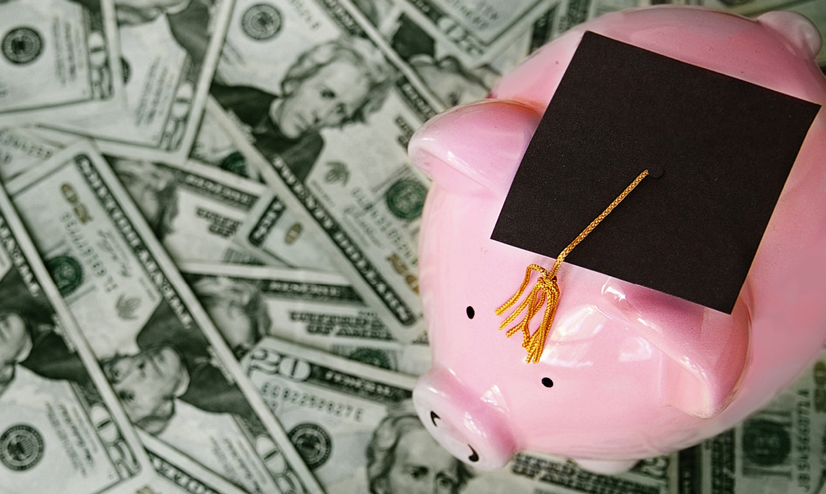 A piggy bank in a graduation hat on a pile of money