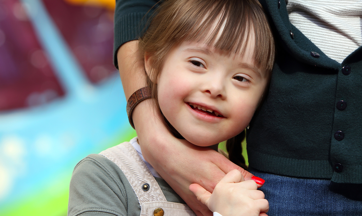 Little girl with special needs hugging a woman