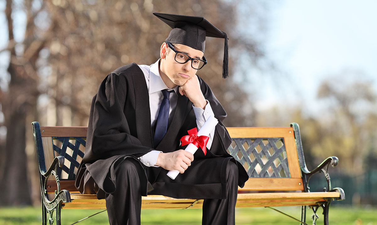 Man sits sadly on park bench in graduation hat and gown