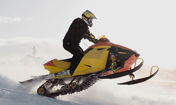 Person on riding a yellow and orange snowmobile