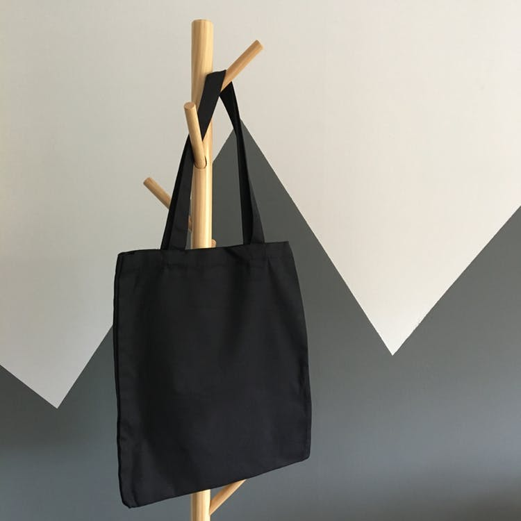 black tote bag on a rack on a white and grey background