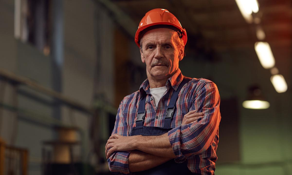 Elderly man in construction hat in factory