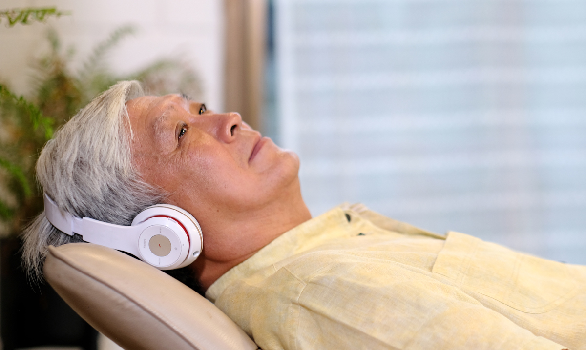 Elderly man laying down listening to headphones