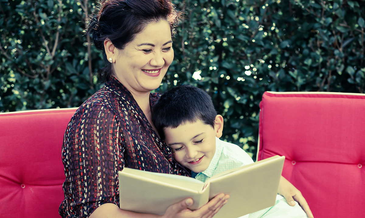 Woman smiling while reading to a child