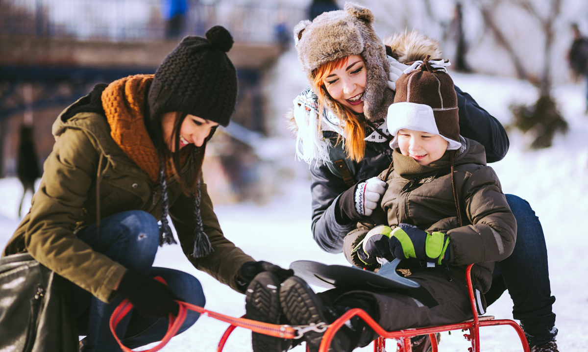 A family of three playing on a sled in the wintertime