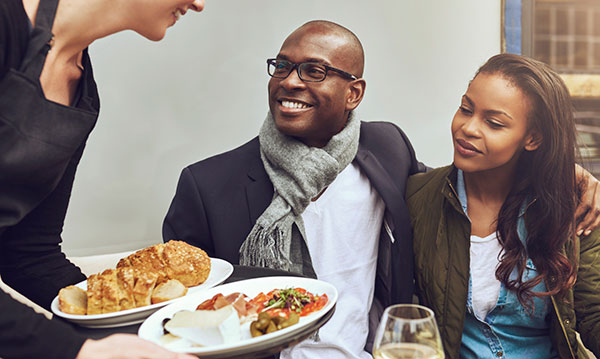 Couple smiling as they are being served food
