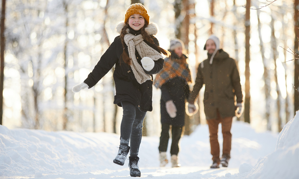 Girl skipping away from her parents in a snowy forest