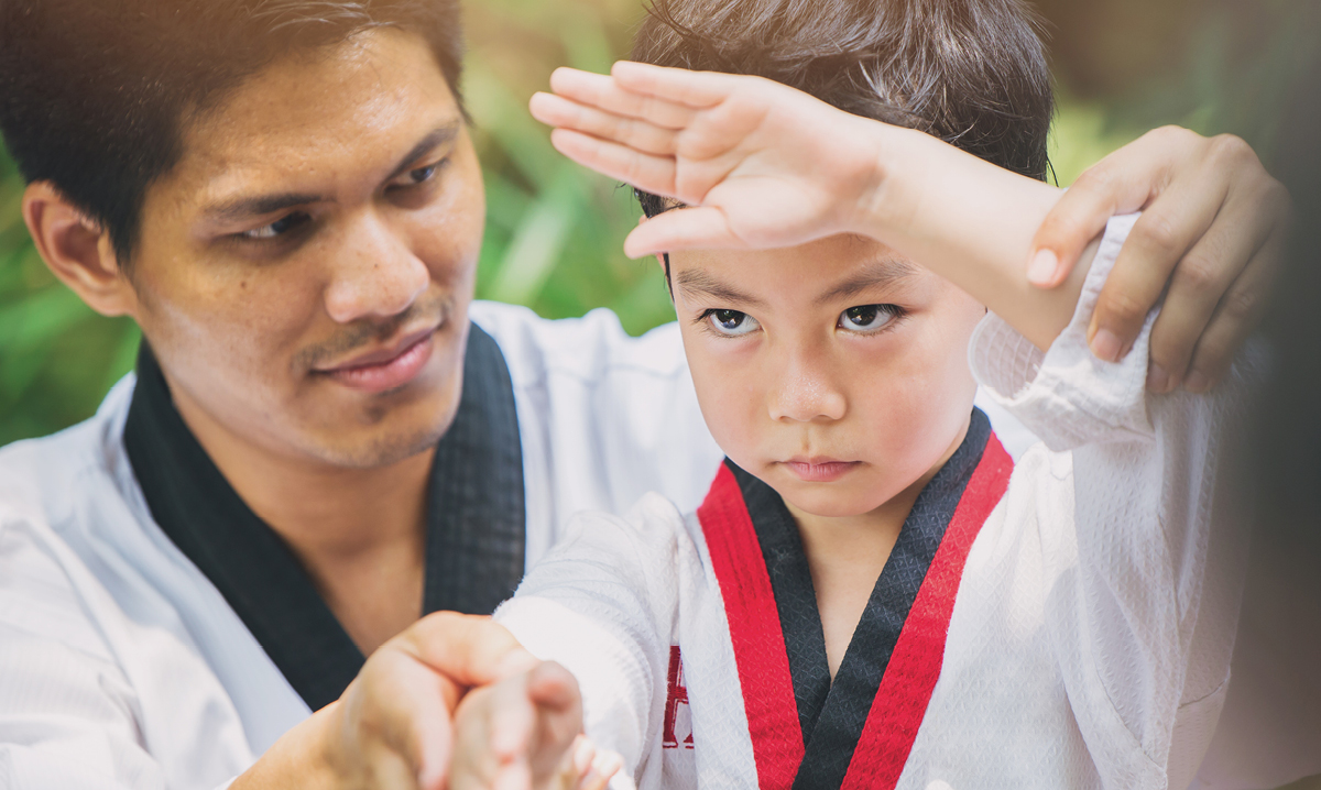 Teacher helping child with a self-defense pose