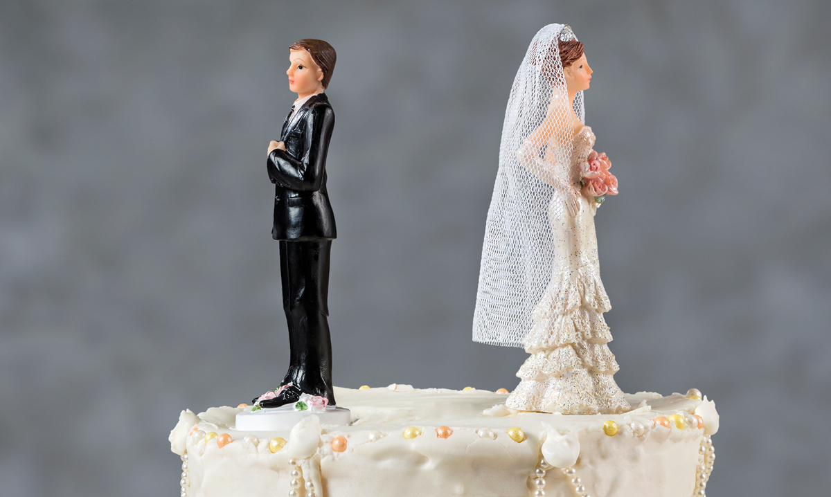 Wedding cake toppers facing away from one another