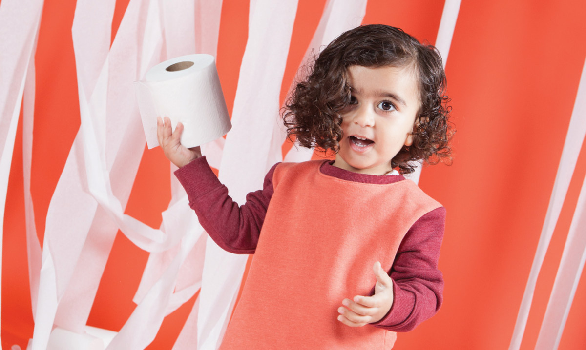 Child holding a roll of toilet paper
