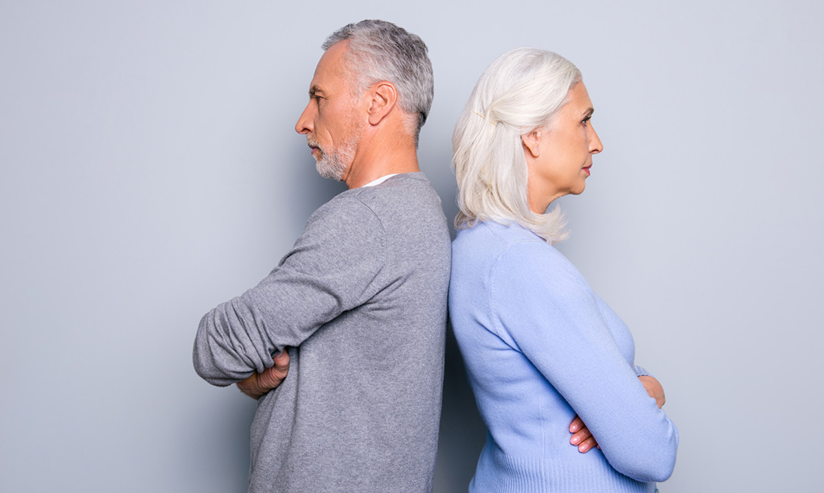 Older man and woman stand back-to-back with arms crossed