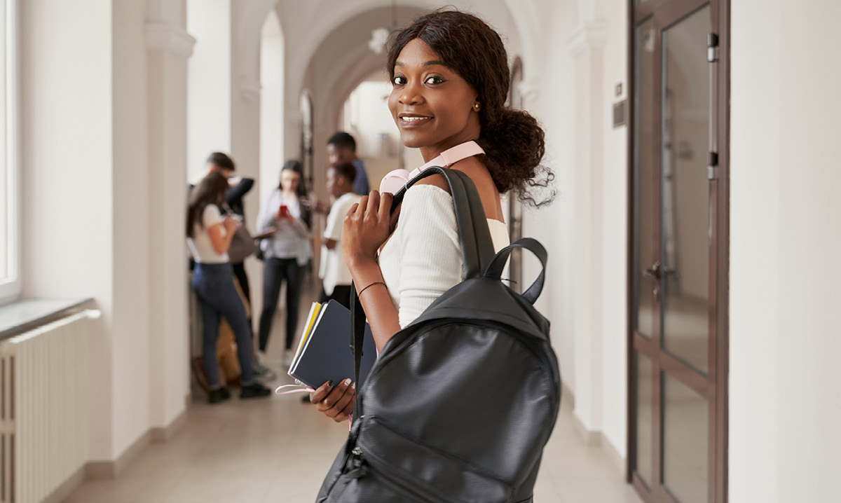 College-aged woman holding a backpack while turning around and looking at the camera