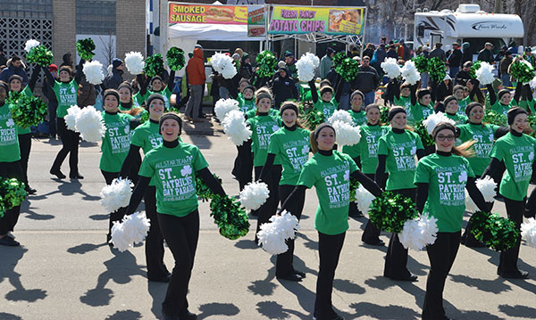A dance team in green with white pompoms at a St. Patrick's Day parade