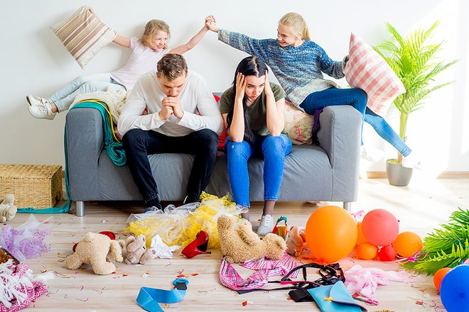 Parents looking stressed surrounded by mess and misbehaving kids