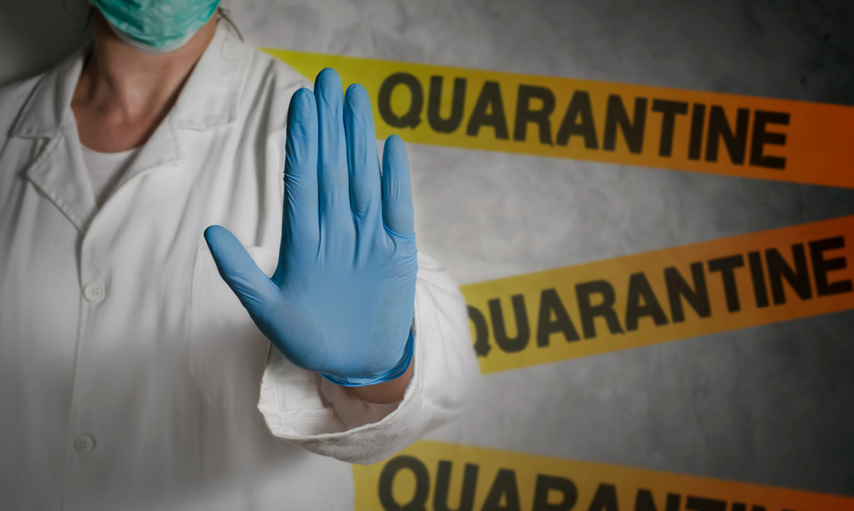 Person in doctor's scrubs holding up a gloved hand in front of three quarantine signs