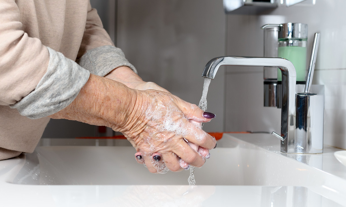 Elderly person washing their hands
