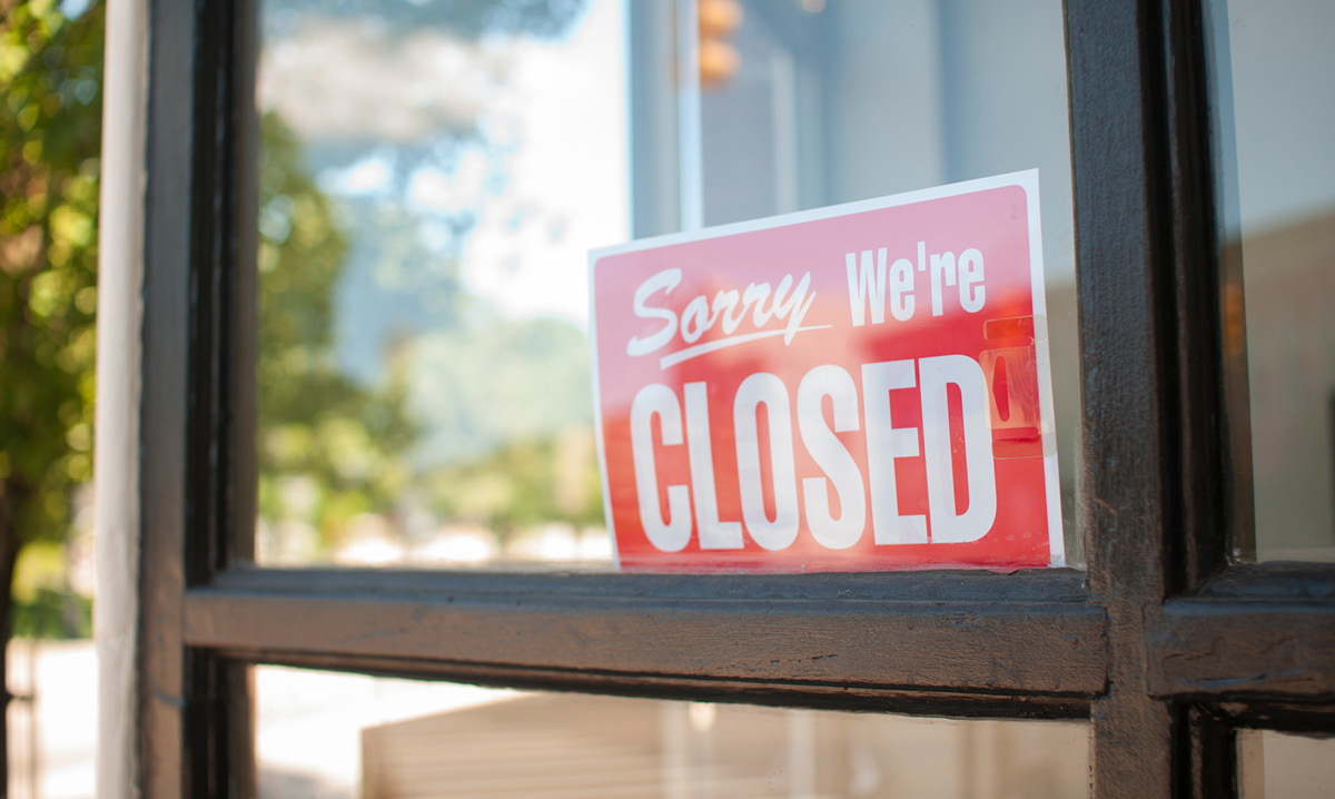 "A ""sorry, we're closed"" sign on a storefront"