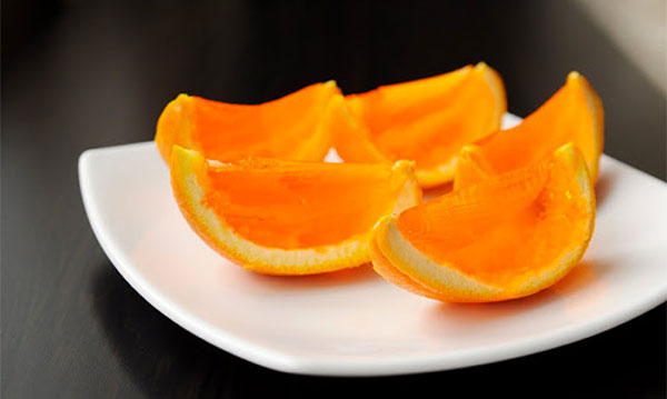Jello-filled orange slices on a white plate