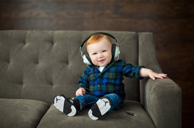 Baby sitting on a couch wearing headphones