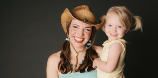Woman in cowboy hat holding little girl