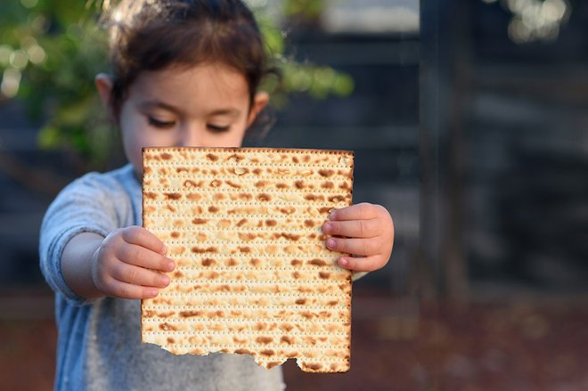 Little girl holding up a passover food item