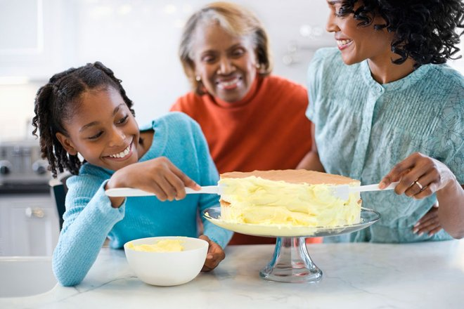 Tween decorating a cake with her mom and grandma