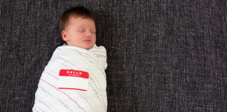 "Sleeping swaddled infant with a ""Hello my name is"" sticker"