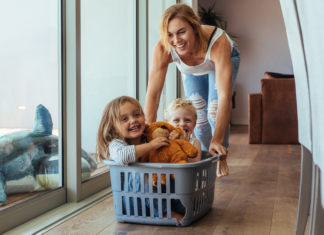 Woman pushing kids in a laundry basket
