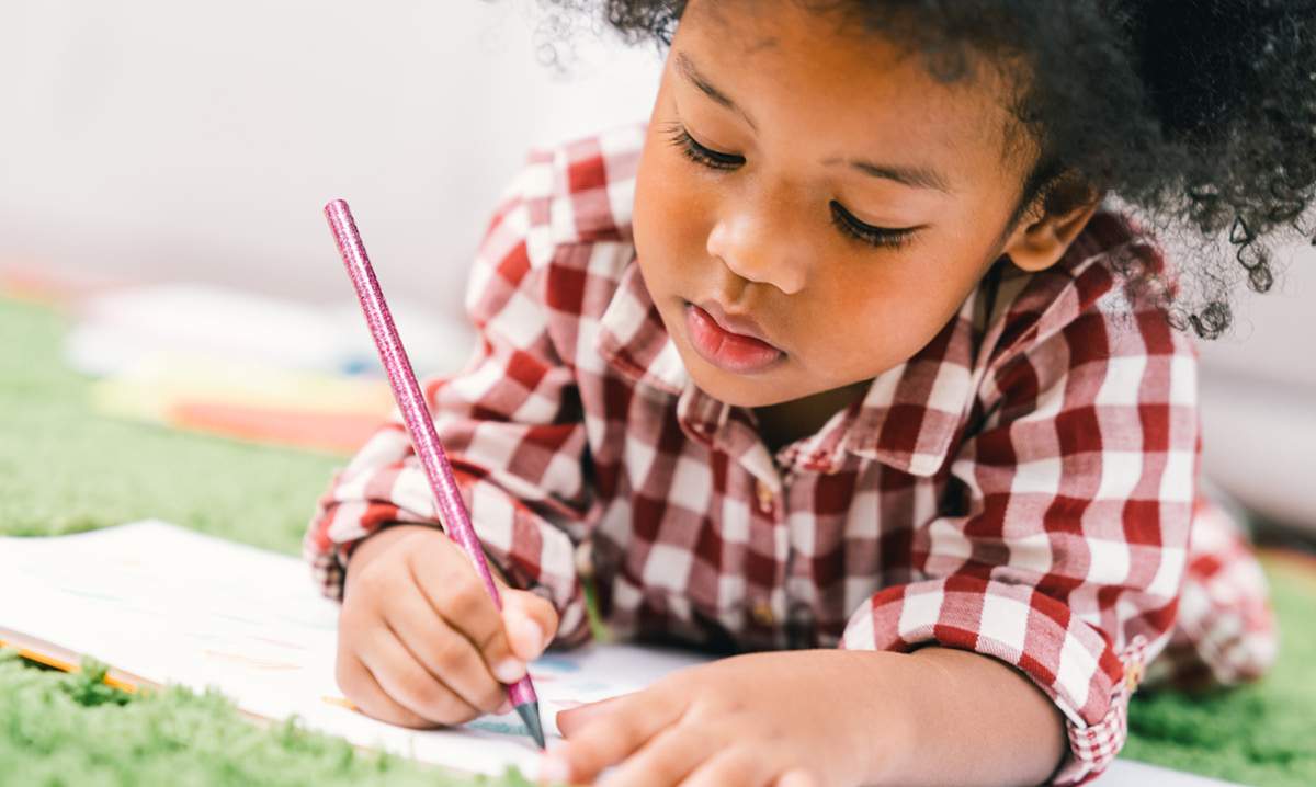 Child coloring with a colored pencil