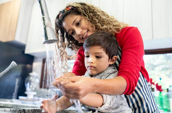 Woman helping a child wash his hands