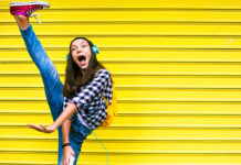 Teen doing a high kick on a yellow background