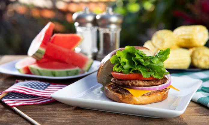 Hamburger, watermelon and corn on a picnic table