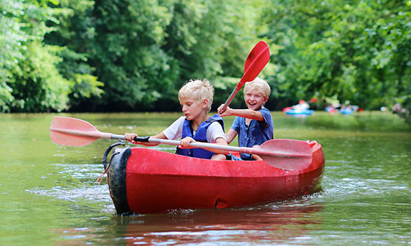 Two kids in a kayak on a river