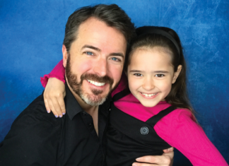 A man and girl smiling on a blue background