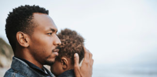 A black man holding a small child