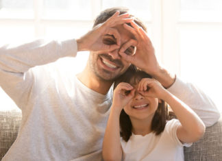 Pretty family father adorable daughter sitting on sofa do funny faces making with fingers eyewear shape like glasses looking through binoculars