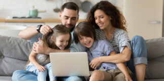 A family of four laughing while on a laptop