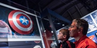 Man and child looking at Captain America shield
