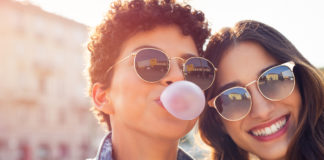 Two girls smiling together while one blows a bubble gum bubble