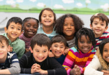 A group of kids of different races smiling together