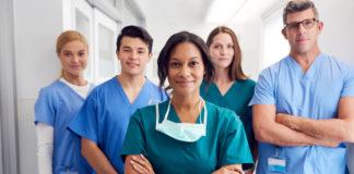 Five doctors looking happy in a hospital