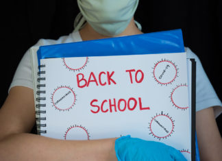 Student in a mask holding a binder that says, back to school