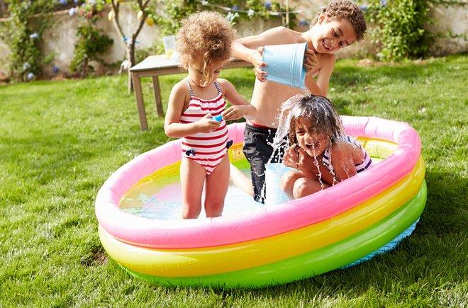 Three kids playing in a kiddie pool