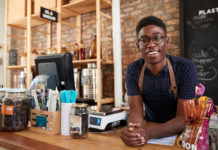 A Black business owner standing at a counter